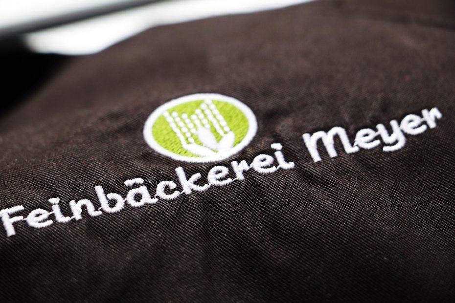 Schürze mit Stickerei des Logos der Feinbäckerei Meyer