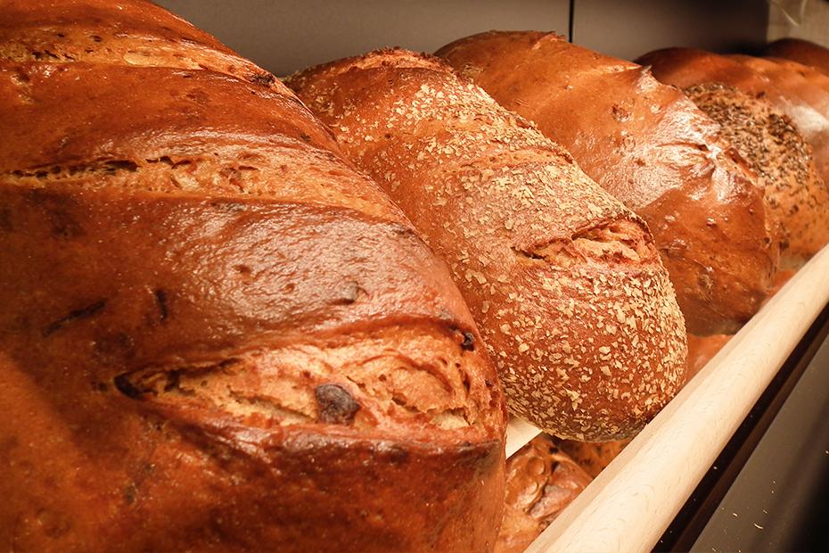 Ausschnitt aus einem Brotregal, auf dem unterschiedliche Brotlaibe liegen