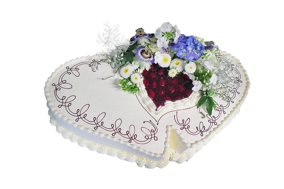 Torte in Herzform mit kleinerem Herz und Blumendekoration obenauf
